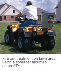 Fire ant treatment on lawn area using a spreader mounted on an ATV.